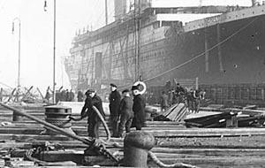 Some workers on the quay; in the background you can see that the TITANIC has two of her funnels installed thus far.