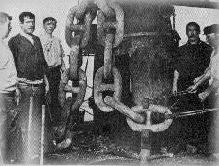 Loyal shipbuilders take a break to pose for this picture by one of her giant anchor chains.
