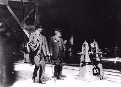 Bruce Ismay & Lord Pirrie walking parallel to the ship's hull, awaiting her launch.